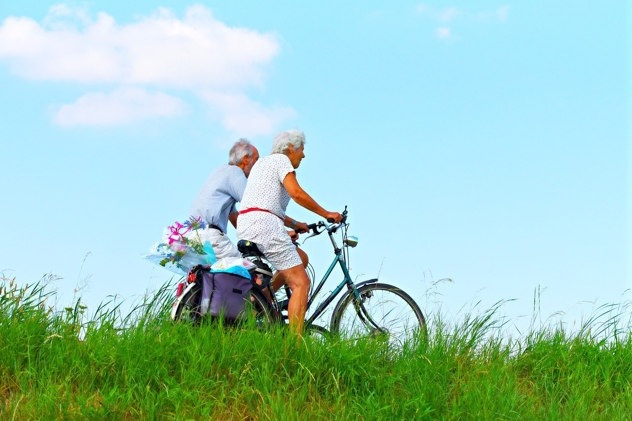 An old couple is cycling outside on a green field